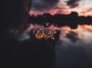atardecer con mujer con luces en las manos